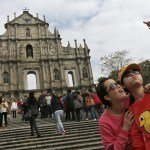 "Mainland Chinese tourists take a picture of them at ""The Ruins of St. Paul's,"" the famous tourist spot, on the second day of the Chinese New Year in Macau, Saturday, Feb. 1, 2014. The Lunar New Year marks the year of the horse this year according to Chinese astrology. (AP Photo/Vincent Yu)"