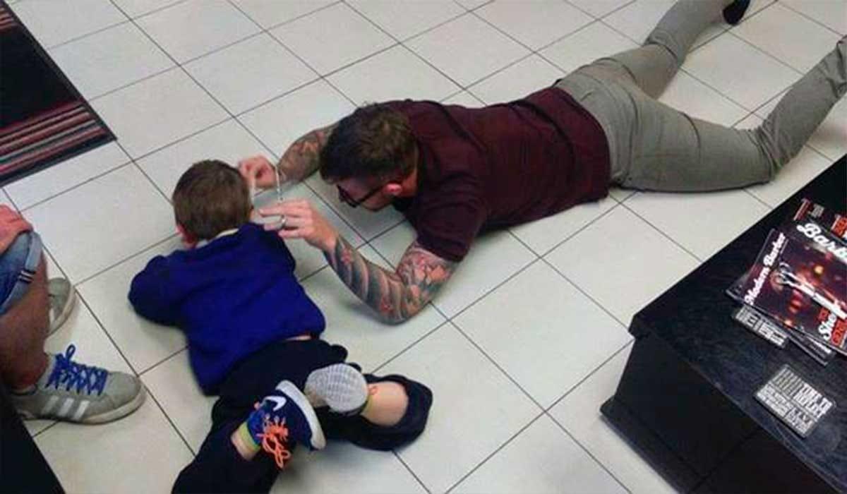 Barbeiro deita no chão para cortar o cabelo de um garoto autista
