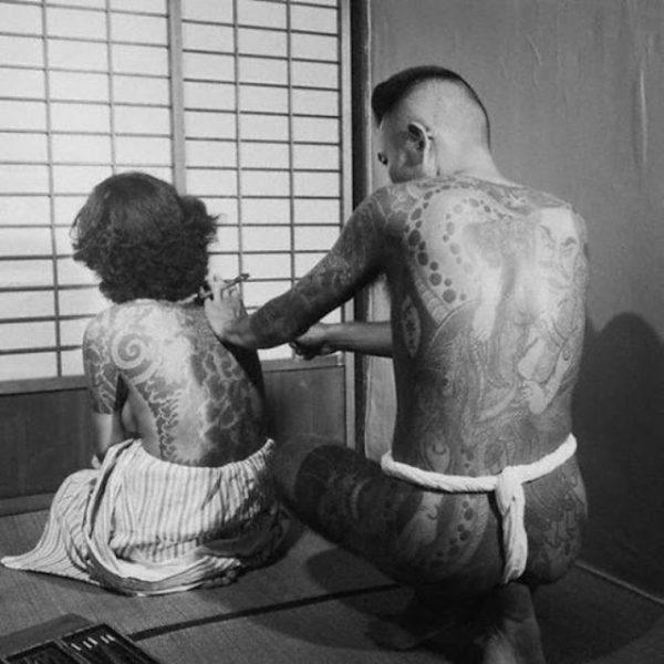MULHER TENDO AS COSTAS COBERTAS COM TATUAGENS TRADICIONAL JAPONESA CERCA DE 1930
