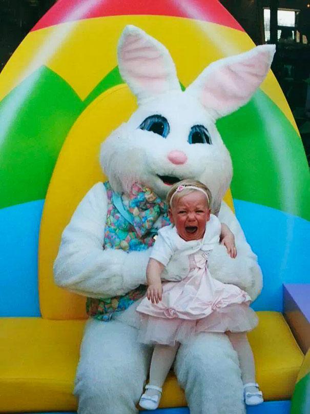 A imagem mostra um coelhinho da Pascoa em tamanho humano envolvendo uma criança nos braços
